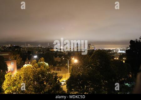 Trees And Buildings In Illuminated City During Night - Stock Photo