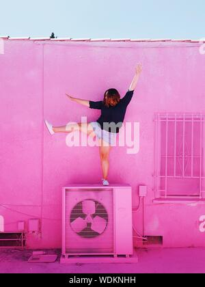 Woman Exercising On Air Conditioner Against Pink Wall During Sunny Day - Stock Photo