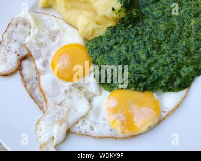 Close-up Of Fried Eggs With Spinach And Smashed Potatoes On Plate - Stock Photo