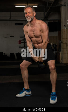 An attractive middle aged man with strong abs is doing kettlebell swings. The shirtless male athlete is doing a functional fitness workout in a gym. - Stock Photo