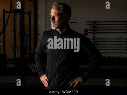 Portrait of an attractive fit middle aged man in a fitness studio. Bearded grey haired man with black sweatshirt jacket is looking into the distance. - Stock Photo