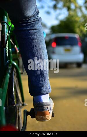 Low Section Of Woman Riding Bicycle On Street - Stock Photo