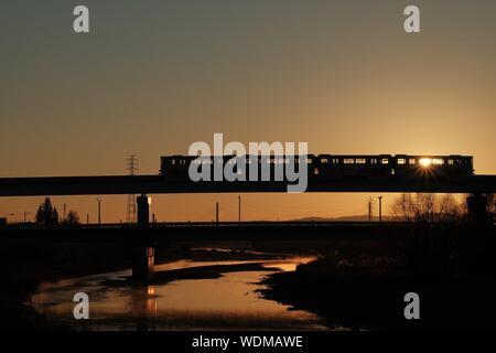 Silhouette Train On Bridge Over Lake Against Sky During Sunset - Stock Photo