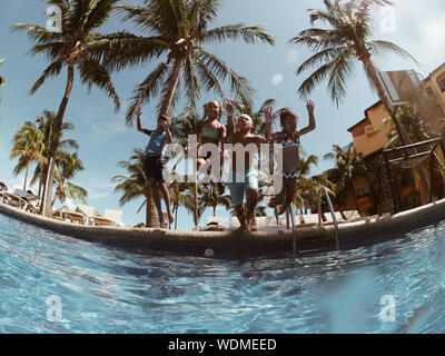 Low Angle View Of Children Jumping In Swimming Pool Against Sky - Stock Photo