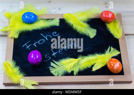 Colorful Easter Eggs With Feathers On Blackboard - Stock Photo