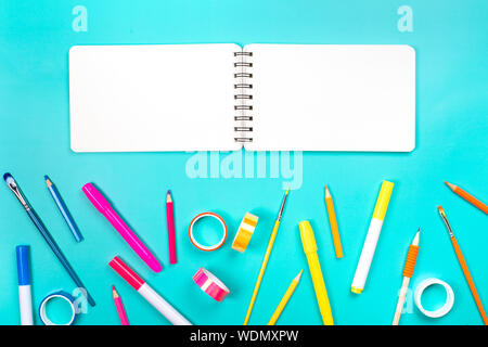 School items as a frame on blue background. Trendy colors, flat lay style. Back to school concept. - Stock Photo