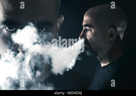 Smoke Emitting From Mature Man Nose While Standing By Friend Against Black Background - Stock Photo