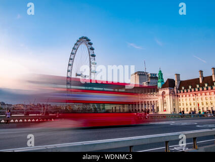 Long exposure photography of Double decker red bus in motion on Westminster Abbey bridge against the Eye of London in England - Stock Photo