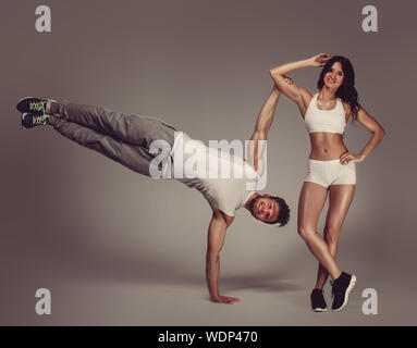 Portrait Of Young Athletic Couple Practicing Acroyoga Against Gray Background - Stock Photo