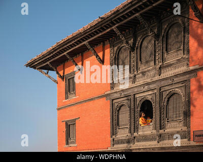 Sadhu holy man sitting in window, reading at Ancient Hindu Nepali Mandir Temple, dedicated to Lord Shiva,  Varanasi, Uttar Pradesh, India, Asia - Stock Photo