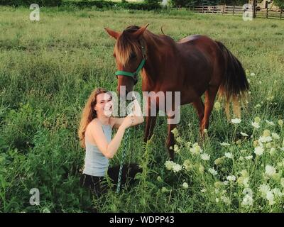 Portrait Of Cheerful Young Woman With Brown Horse On Grassy Field At Farm - Stock Photo