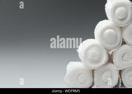 Close-up Of Rolled Up Bandages Over Gray Background - Stock Photo