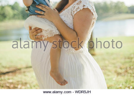 Woman in white lace dress carrying child - Stock Photo