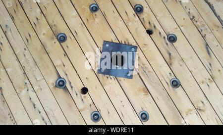 High Angle View Of Bolts And Nuts On Wooden Table - Stock Photo