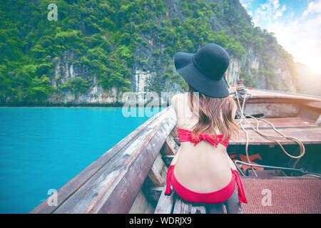 Rear View Of Woman Wearing Red Bikini While Sitting In Boat At Beach - Stock Photo