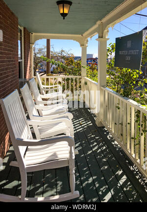 Typical historical New England inn, complete with porch, four rocking chairs and wood railings in autumn. Wood and brick 19th century architecture. - Stock Photo
