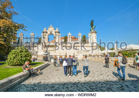 Tourists walk together and enjoy a sunny day in early autumn at the Buda Castle Hill District near the Turul bird statue in Budapest Hungary - Stock Photo