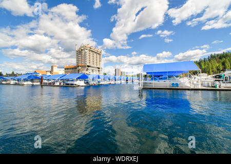A view from the floating boardwalk of the marina full with boats and the Coeur d'Alene Resort on Lake Coeur d'Alene. - Stock Photo