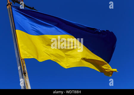Low Angle View Of Ukrainian Flag Waving Against Blue Sky - Stock Photo