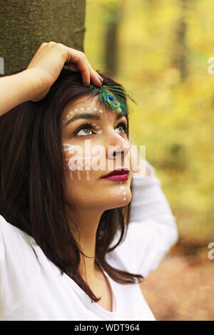 Close-up Of Young Woman With Painted Face Holding Peacock Feather - Stock Photo