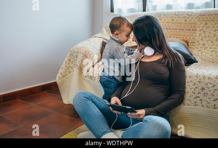 Mother Looking At Son While Using Digital Tablet At Home - Stock Photo