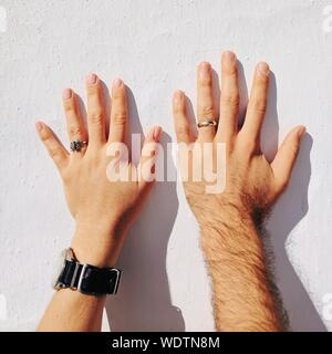 Cropped Hands Of Couple Wearing Wedding Rings While Touching White Wall - Stock Photo