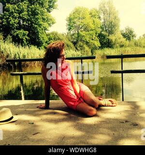 Young Woman Sitting By Railing Against Lake - Stock Photo