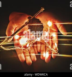 Cropped Hands Of Woman Holding String Lights And Pine Cone With Light Trail In Dark - Stock Photo