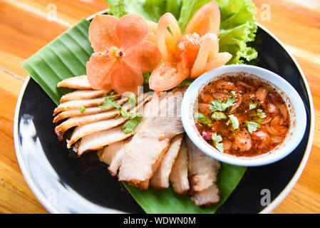 Roasted pork / sliced baked pork grilled with spicy sauce and sticky rice herbs spices ingredients fresh vegetable served on plate in the wooden table - Stock Photo