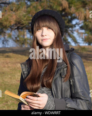Close-up Portrait Of Teenager With Lip Piercing Holding Book - Stock Photo
