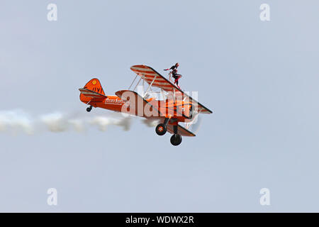 Part of the Aerosuperbatics Wingwalkers this 1940's biplane with the young lady strapped on top wows the crowd at Eastbourne's International Airshow. - Stock Photo