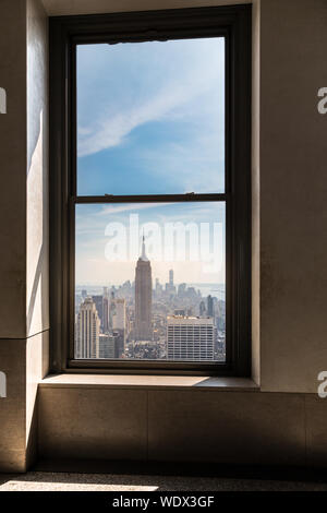 Empire State Building Seen Through Glass Window - Stock Photo