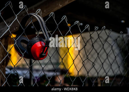 Close-up Of Earmuffs Hanging Chainlink Fence - Stock Photo