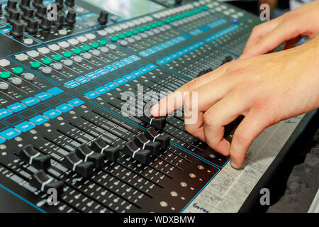 Hand on a mixer, operating the leader Music console - Stock Photo