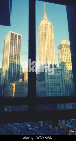 Low Angle View Of Empire State Building Seen Through Glass - Stock Photo