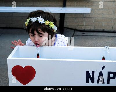 Girl Drinking Water At Drinking Fountain In Park - Stock Photo