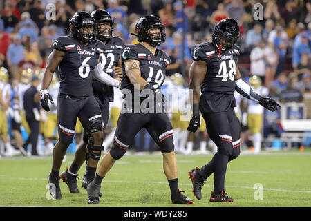 August 29, 2019: Cincinnati's Ethan Tucky (19) struts to celebrate his sack with teammates Perry Young (6) and Kevin Mouhon (48) during an NCAA football game between the Cincinnati Bearcats and the UCLA Bruins at Nippert Stadium in Cincinnati, Ohio. Kevin Schultz/CSM