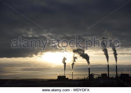Smoke Emitting From Chimneys Against Sky At Sunset - Stock Photo