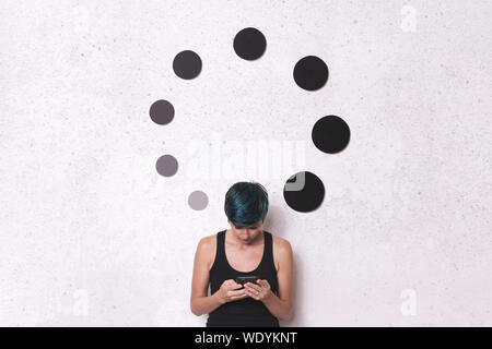 Woman Using Phone While Standing By Circular Shape Decorations On Wall - Stock Photo