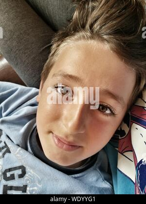 Close-up Portrait Of Teenage Boy Lying On Bed - Stock Photo