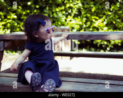 Cute Baby Girl Wearing Sunglasses While Sitting On Wooden Bench - Stock Photo