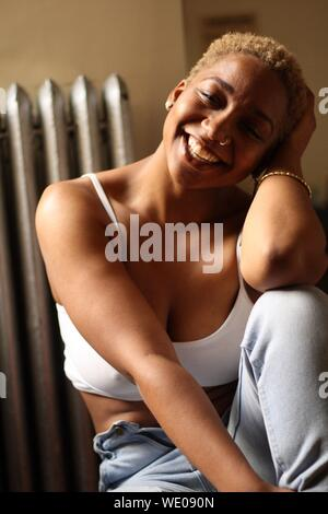 Portrait Of Happy Mid Adult Woman Sitting By Radiator At Home - Stock Photo