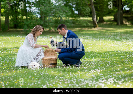 Side View Of Bridegroom With Bride Holding Champagne Bottle By Basket On Grassy Field - Stock Photo