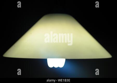 Close-up Of Illuminated Pendant Light In Darkroom - Stock Photo