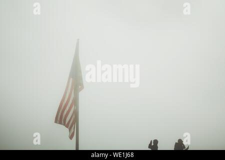 Low Angle View American Flag In Foggy Weather - Stock Photo