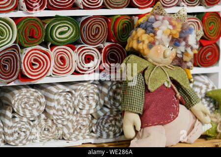 Close-up Of Stuffed Toy By Rolled Up Fabrics In Shelves At Store For Sale - Stock Photo