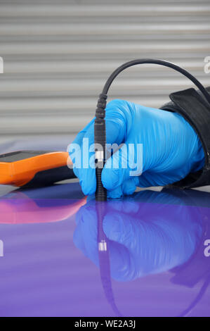 Person using probe, with digital tester, to measure the paint thickness microns on a painted metal panel. Person wearing protective gloves. - Stock Photo