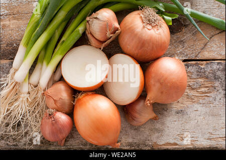 Assorted farm fresh onions on a rustic wooden table with spring onions, brown onions and shallots , with one onion cut in half in the centre of the ar - Stock Photo