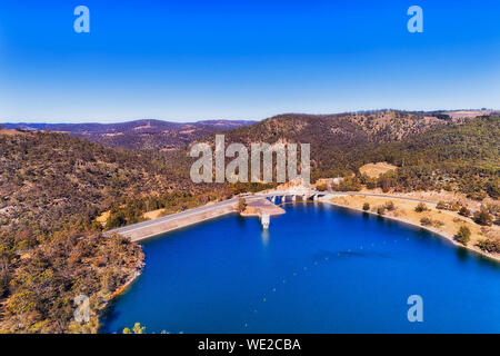 Blue waters of Lake Lyell under blue sky in Blue Mountains of Australia when a dam on Coxs river forms reservoir between hill ranges seen from above.