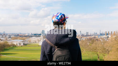 Rear View Of Man Wearing Cap While Standing Against Field In City - Stock Photo